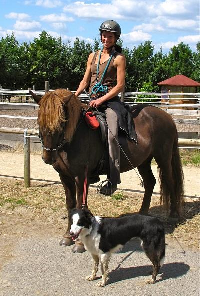 Reiten trotz Querschnittslähmung: Corinna sitzt auf ihrem Pferd und hat ihren Hund an der Leine